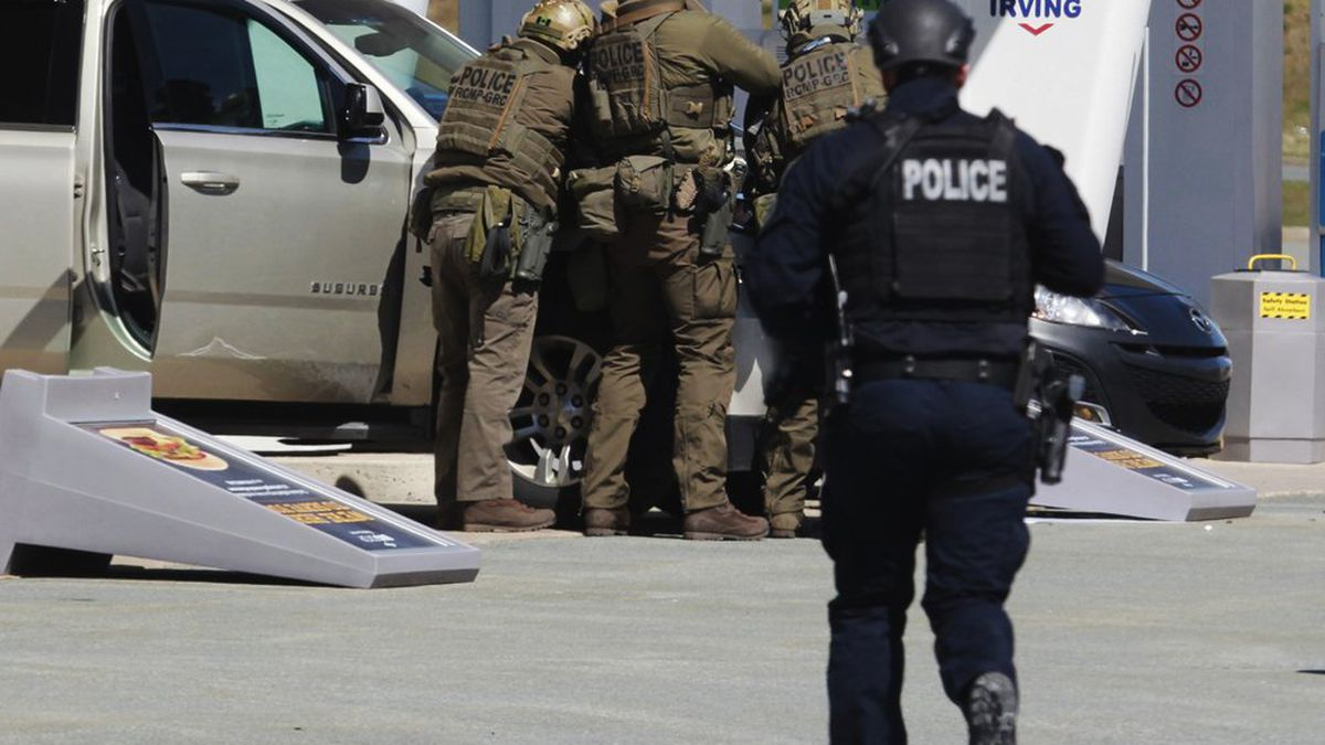 Royal Canadian Mounted Police officers surround a suspect at a gas station in Enfield, Nova Scotia on Sunday April 19, 2020. Canadian police say multiple people are dead plus the suspect after a shooting rampage across the province of Nova Scotia. It was the deadliest shooting in Canada in 30 years. (Tim Krochak/The Canadian Press via AP)