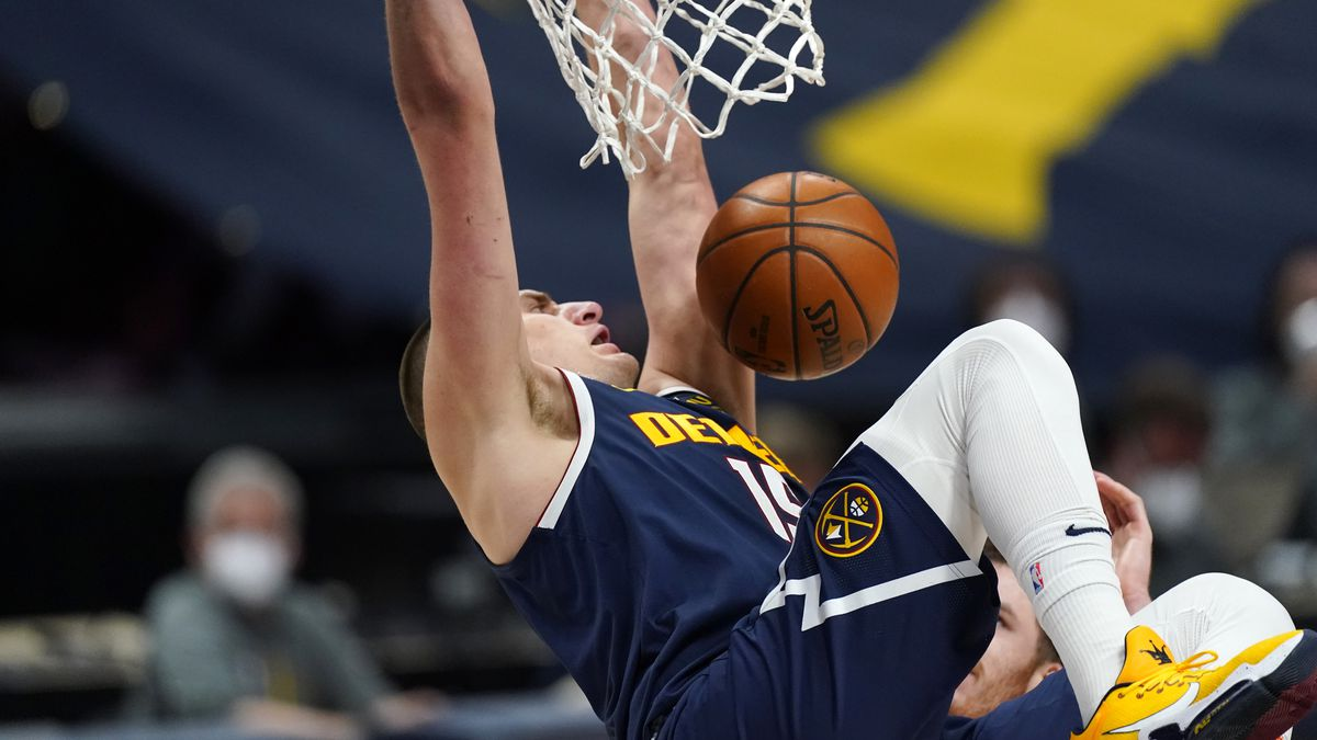 Denver Nuggets center Nikola Jokic hangs from the rim after dunking against the San Antonio...