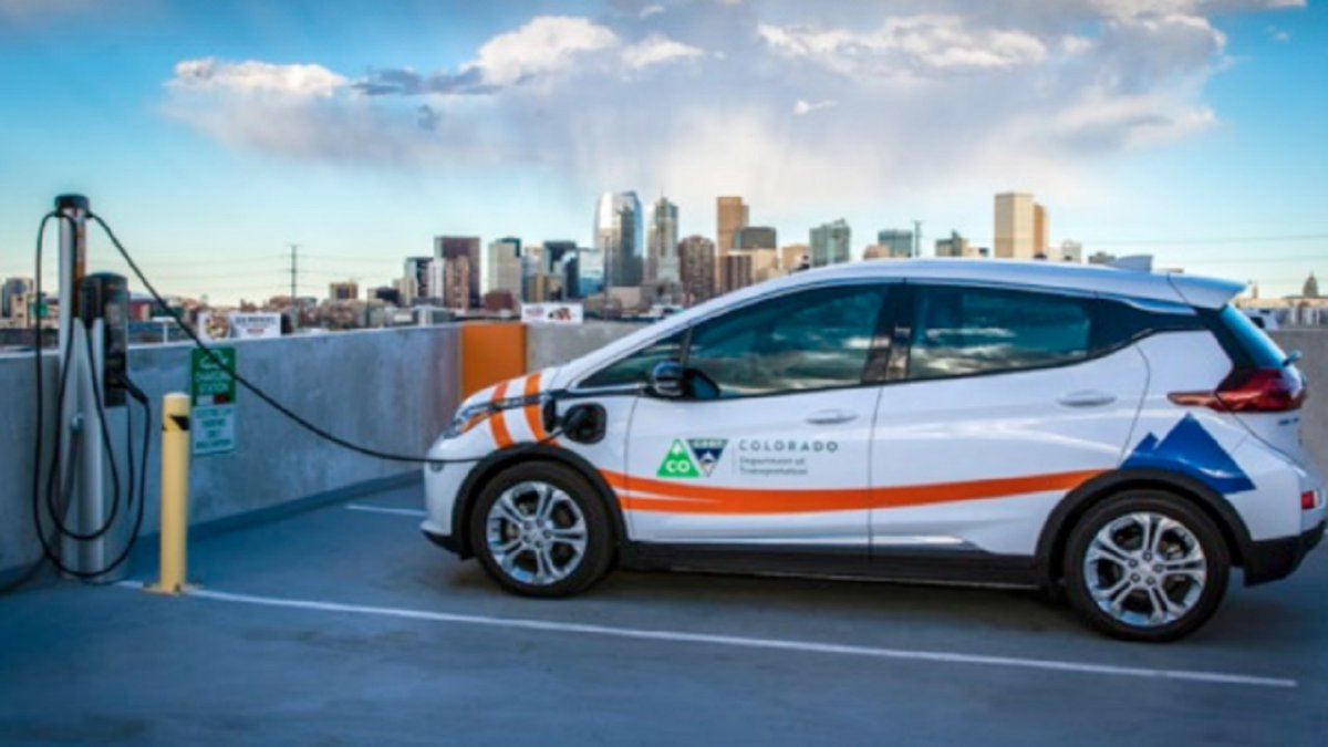 An electric vehicle charging with the City of  Denver in the background.